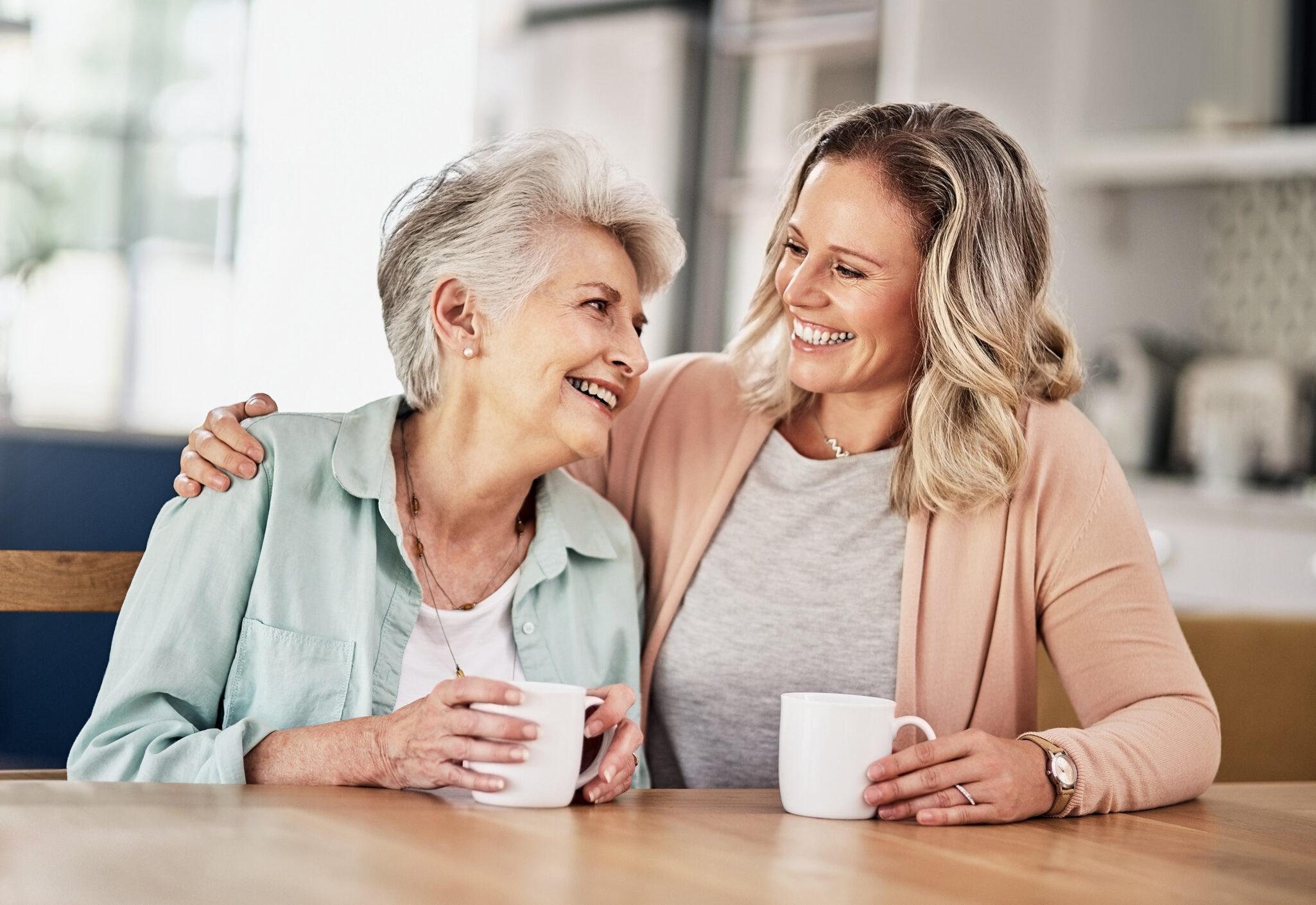 Senior woman hugging daughter while enjoying coffee