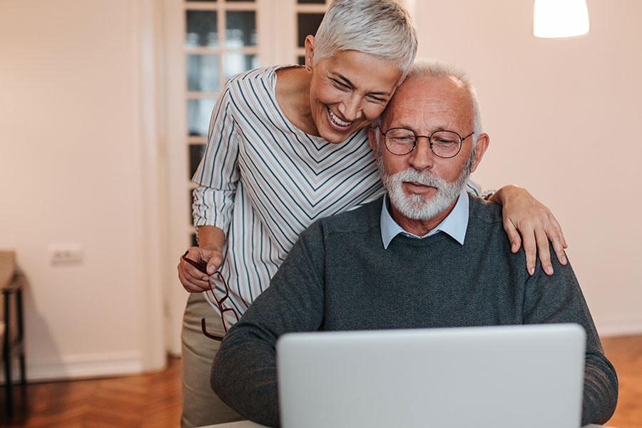 A senior couple looking at something on a laptop