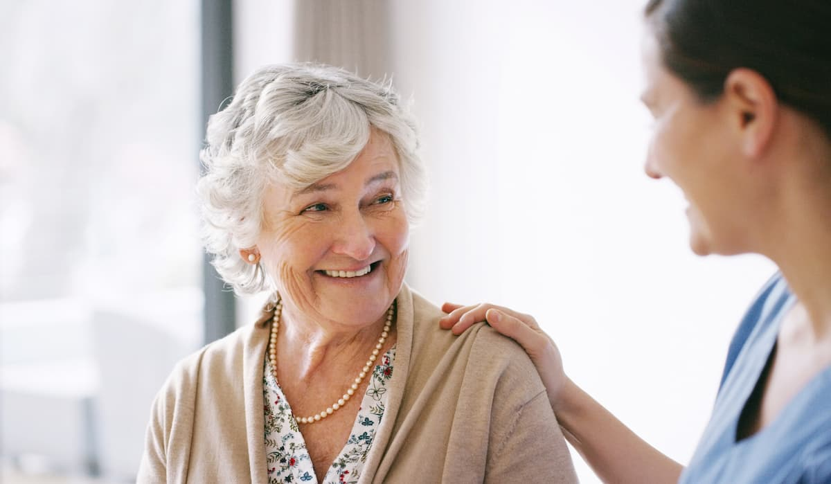 Older woman smiling at younger female caregiver who has her hand on her shoulder.