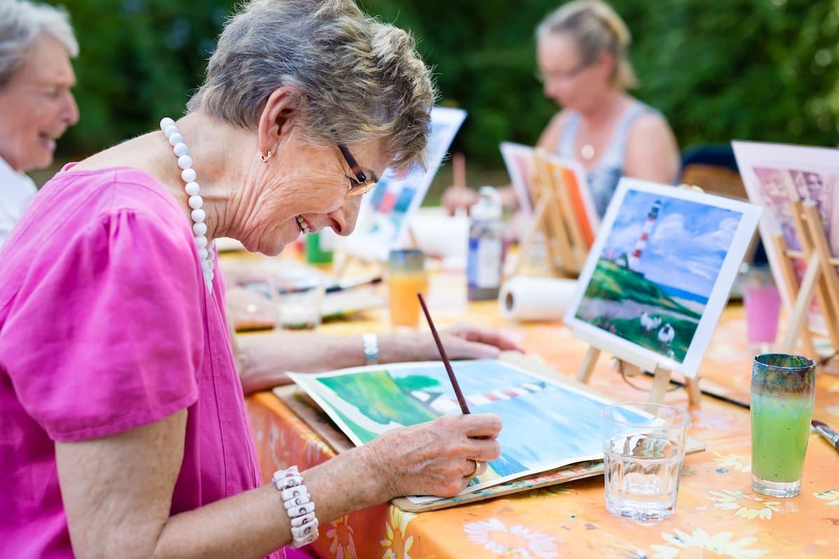 Senior women taking part in outdoor group arts class.