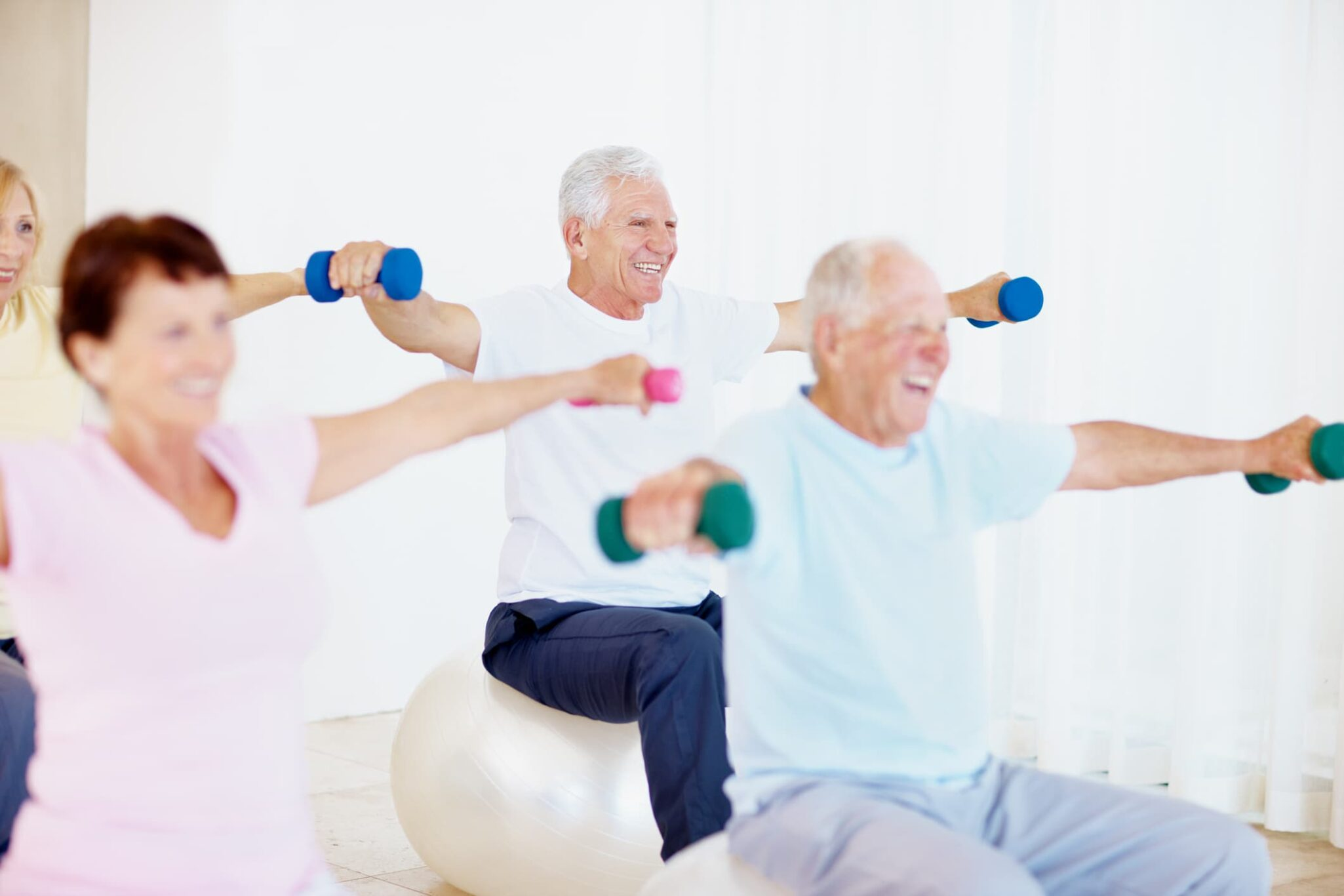 Group of older adults smiling while lifting weights in a strength training class.